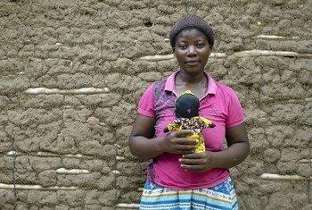 Mkimbizi Kituza kutoka Jamhuri ya Kidemokrasia ya Congo, DRC akiwa kambini Maratane nchiin Msumbiji huku akiwa amebeba mwanaserere anayetengeneza na kumpatia fedha na uponyaji.