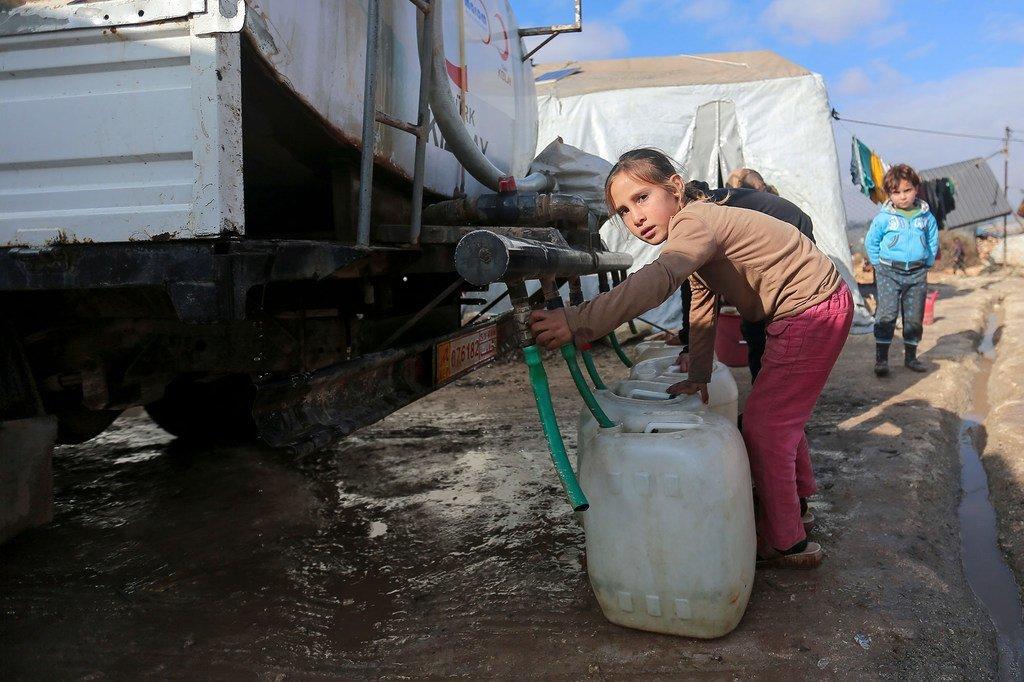 Une jeune fille récupère l'eau d'un camion-citerne dans un camp de personnes déplacées dans le nord-ouest de la Syrie.