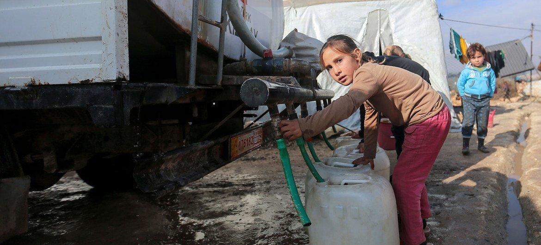 فتاة تجمع المياه من شاحنة محملة بالمياه في أحد مخيمات النازحين داخليا في شمال غرب سوريا.