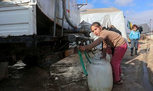 A young girl collects water from a tanker truck in an IDP camp in northwest Syria.