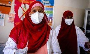 Mhudumu wa afya akijiandaa kumchoma mhudumu mwingine wa afya chanjo ya COVID-19 kwenye hospitali moja huko Mogadishu nchini Somalia.