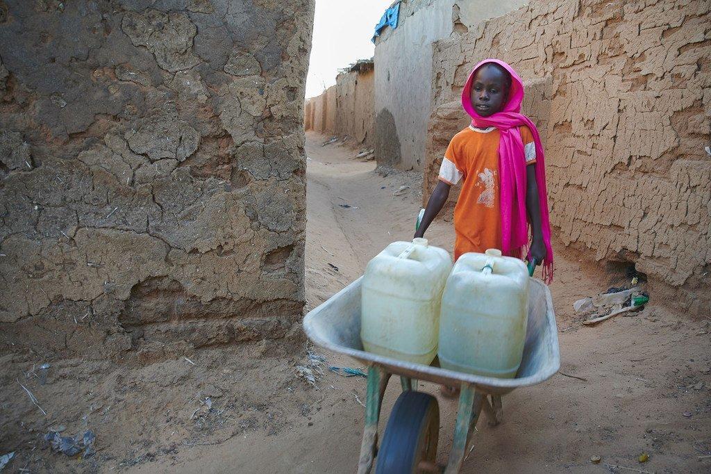 Mtoto wa kike mwenye umri wa miaka 9 akisukuma tololi likiwa na madumu ya maji kwenye kambi ya wakimbizi wa ndani huko Darfur nchini Sudan