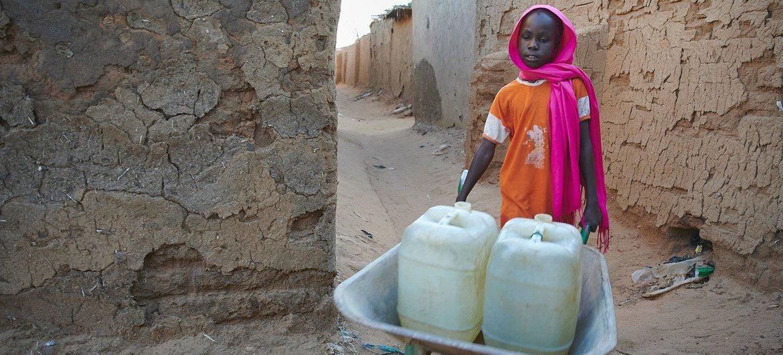 在苏丹达尔富尔境内流离失所者营地,一名九岁女孩推着一辆装满水的手推车。