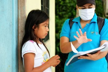 An eleven-year-old girl in Ecuador receives a study guide during the COVID-19 pandemic when schools closed.