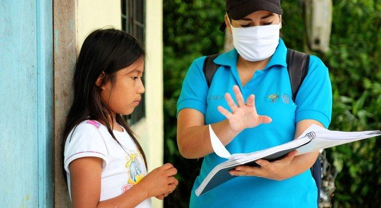 Una niña de 11 años en Ecuador recibe una guía para estudiar durante el cierre de escuelas por la pandemia de COVID-19