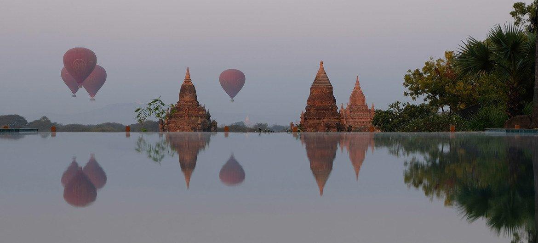 Balões de ar quente carregando turistas ao nascer do sol em Bagan, Mianmar