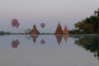Des montgolfières transportant des touristes survolent des pagodes à Bagan, au Myanmar, au lever du soleil.