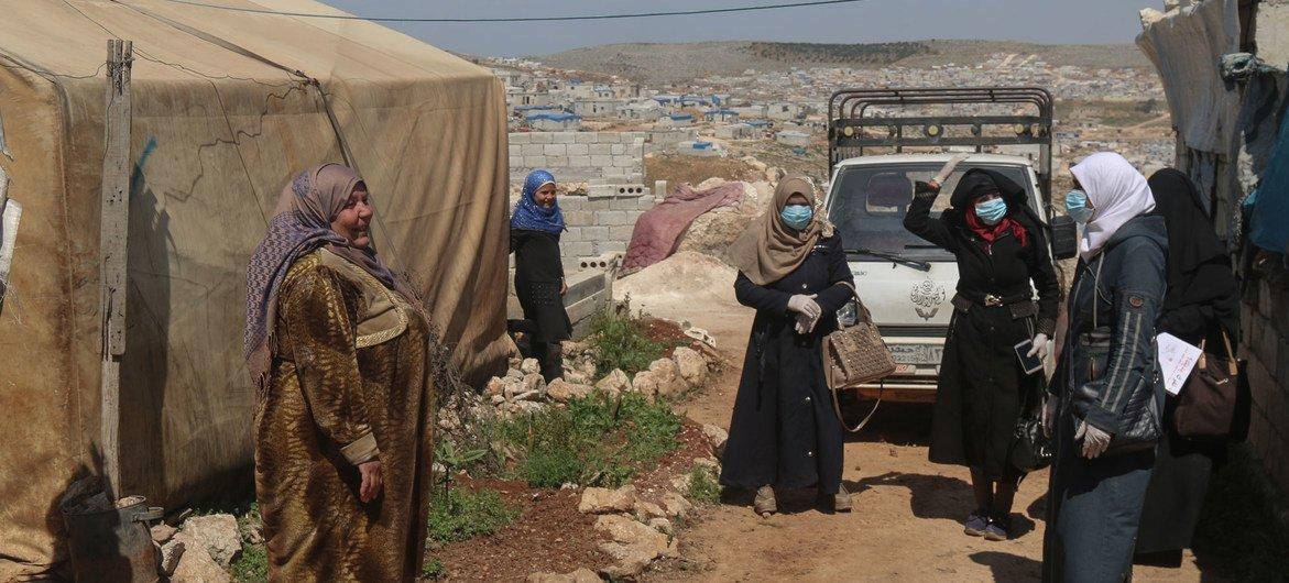نازحون سوريون يرتدون كمامات ويمارسون التباعد الجسدي.