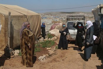 Standing on the left, a volunteer working to raise awareness on COVID-19 at an IDP camp in northern Idlib, Syria. Displaced from Homs herself, she knows the importance of helping protect the IDPs.