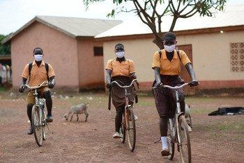 Des élèves ghanéens portant un masque sur leurs visages sur le chemin de l'école