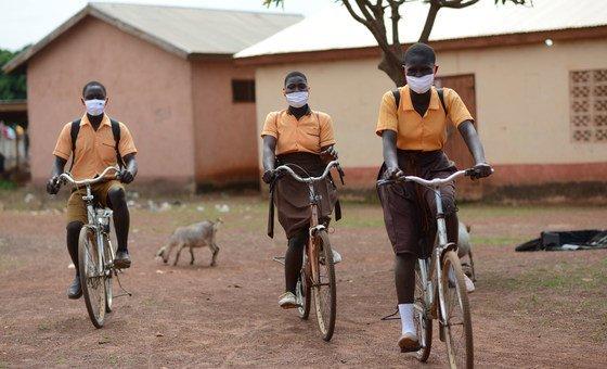 Alunos em Gana usando máscaras faciais a caminho da escola.