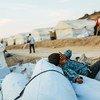 希腊莱斯沃斯岛难民营火灾后,一名来自阿富汗的男孩正在临时安置点内休息。