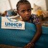 Un jeune réfugié éthiopien ramasse un matelas sur un site de transit à Hamdayet, au Soudan.