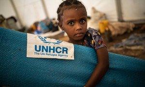 لاجئة إثيوبية صغيرة تستلم فرشة في موقع عبور في الحمداييت، السودان.