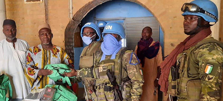 Des casques bleus du  contingent ivoirien de la MINUSMA avec la population locale du Mali.
