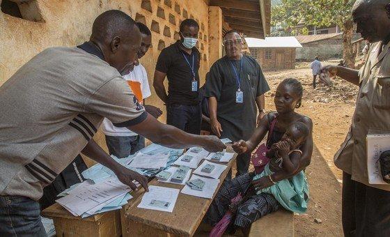 Dans un centre de vote de la capitale Bangui, une jeune femme centrafricaine vient retirer sa carte d'électeur en vue des élections présidentielle et législatives du 27 décembre 2020