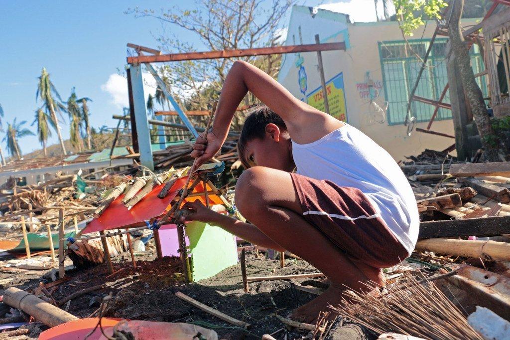 Un niño construye una casita con basura y escombros. Su hogar fue completamente destruido con el paso del Tifón Goni en las Filipinas.