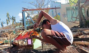 A boy makes a small house using plastic and debris. His home was completely swept away when Typhoon Goni hit the Philippines in November 2020.