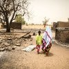 A woman and her daughter walk past the remains of destroyed homes during the March 2019 attack on Ogossagou village by armed Dogon men in which over 150 civilians were killed.