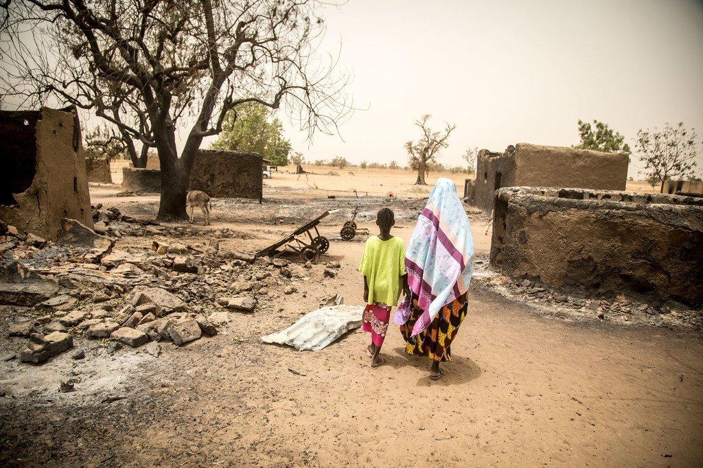 Une femme et sa fille passent devant les restes de maisons détruites lors de l'attaque de mars 2019 du village d'Ogossagou par des hommes armés Dogon, au cours de laquelle plus de 150 civils ont été tués.