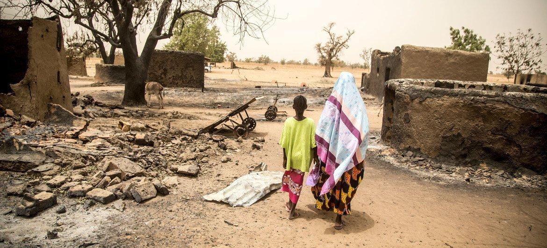 امرأة وابنتها تمشيان بالقرب من أنقاض منازل مدمرة خلال هجوم مارس 2019 على قرية أوغوساغو من قبل رجال الدوغون المسلحين حيث قتل أكثر من 150 مدنياً.