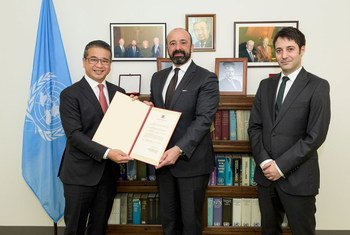 Edwin Tong Chun Fai (left) of Singapore presents instruments of ratification to UN Legal Counsel Miguel de Serpa Soares. At right is David Nanopoulos of the Office of Legal Affairs.