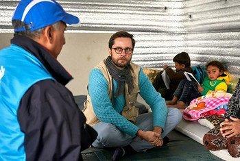 让-尼古拉斯在约旦阿兹拉克难民营的避难所与叙利亚难民瓦尔达和她的五个孩子交谈。