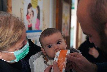 طفل يبلغ من العمر تسعة أشهر يأكل معجون الفول السوداني المغذي في عيادة في طرطوس بسوريا.