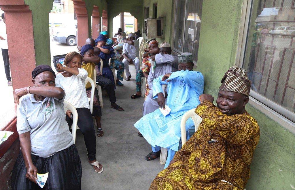 مجموعة من سكان ولاية لاغوس في نيجيريا يتبعون تعايمات العطس في مرفقيهم أثناء حملة التوعية للوقاية من الفيروسات التاجية.