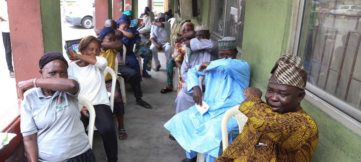 People living in Lagos State in Nigeria, simulate  sneezing into their elbows during a coronavirus prevention campaign.