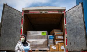 Trabajadora de salud de Indonesia ayuda a descargar el equipo médico que les envió UNICEF para cuidar a los pacientes de COVID-19.