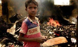 طفل يبلغ من العمر 10 سنوات يقف وسط الركام في مخيم كوتوبالونغ للاجئين في جنوب بنغلاديش. ويظهر خلفه بقايا النيران المشتعلة التي خلفها حريق هائل في المخيم. 23 آذار/مارس 2021