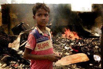 3月23日,一个十岁的孩子站在孟加拉国南部库图帕隆难民营的废墟中。 大火在营地中肆虐了一天,在他身后,仍有火在燃烧。