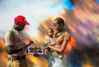 An UNMAS community liaison officer, talks to a woman in South Sudan about the danger of mines.