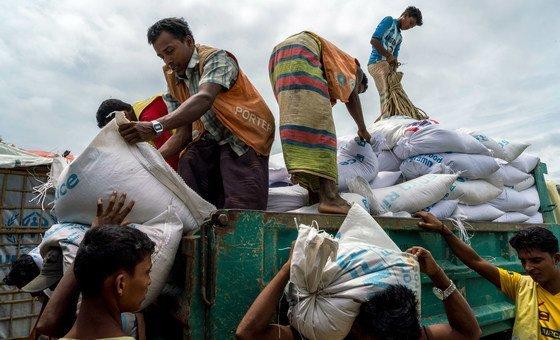 世界粮食计划署在孟加拉国的一个难民营的分发站,罗辛亚难民工人正在分发一袋袋大米和小扁豆。