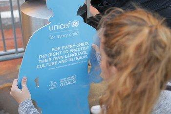 Una niña obervando un muñeco de cartón en forma de chico que forma parte de la instalación de UNICEF sobre la Convención sobre los Derechos del Niño, expuesta fuera de la Sede de las Naciones Unidas.