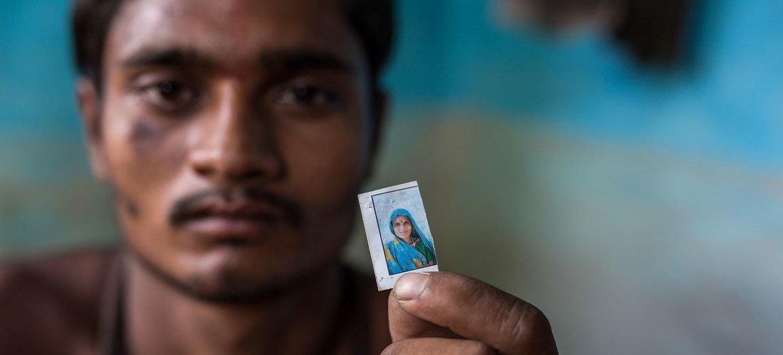印度的一名移民工人拿着母亲的照片。他的母亲在新冠大流行期间返乡途中在一场交通事故中丧生。