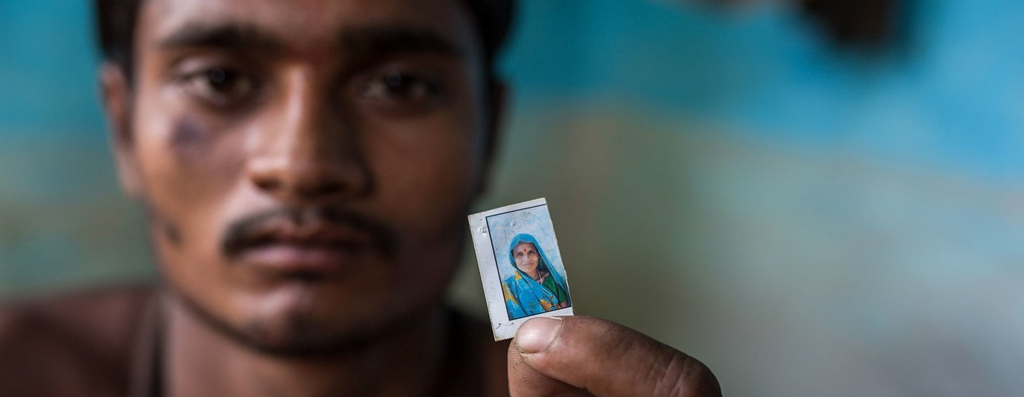 A migrant labourer in India holds a photo of his mother who was killed in a road accident as they returned home during the COVID-19 pandemic.
