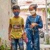 طفلان يسيران في الهند يرتديان الأقنعة لحماية أنفسهما من كوفيد-19.