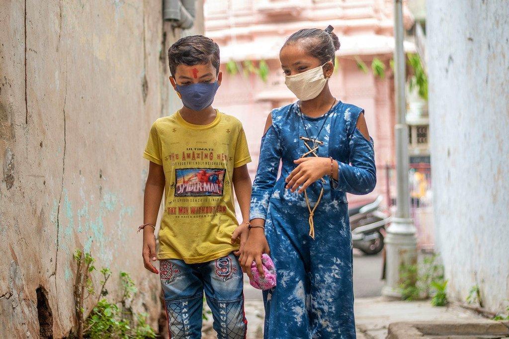 Un jeune garçon et une jeune fille en Inde se protègent contre la Covid-19 en portant des masques faciaux.