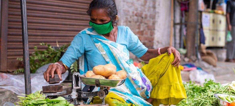 سيّدة تبيع الخضراوات والفاكهة في الشارع، وترتدي القناع الواقي في خضم جائحة كوفيد-19.