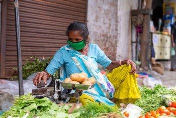Une vendeuse dans la rue en Inde porte un masque pour se protéger de la Covid-19.