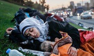 Una madre sin hogar duerme con su bebé en la hierba cercana a una autopista.
