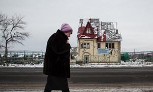 一名乌克兰女性走过一栋在冲突中被毁的房屋。
