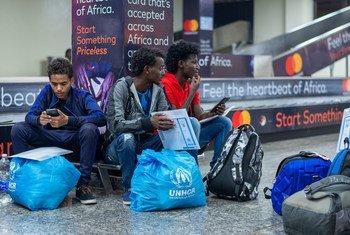 Vijana watatu wakimbizi wakisubiri katika uwanja wa ndege wa Kigali Rwanda baada ya kuhamishwa kwa njia ya ndege kutoka Libya.