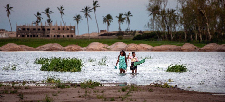 Une femme et un enfant marchent dans une zone inondée au Mozambique après que le cyclone Eloise a décplacé des milliers de personnes.