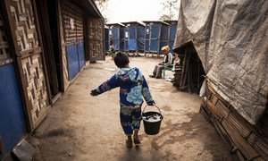 About one million people, affected by conflict and natural disasters, are in need of humanitarian aid and protection in Myanmar. Pictured here, a 12-year-old child fetches water for his household at an IDP camp in Kachin state. (file photo)