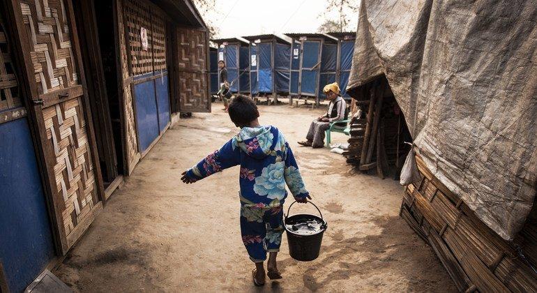 طفل في ميانمار ينقل الماء بدلو في أحد مخيمات النازحين داخليا (صورة من الأرشيف).