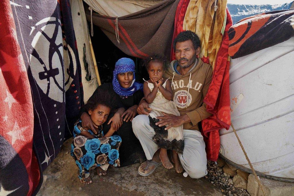 فضل وفاطمة وأولادهما أمام خيمتهم. عاشت العائلة هنا في مدرسة الفجر، التورة، منذ خمس سنوات بعد نزوحها من مدينة تعز عام 2015.