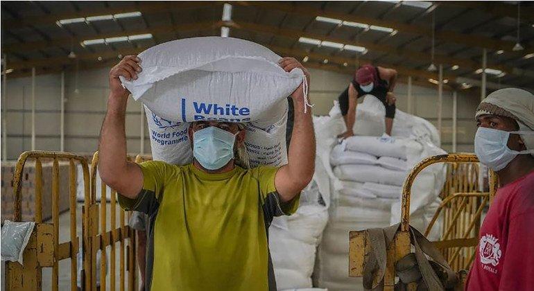 عامل في مستودع لبرنامج الأغذية العالمي في صنعاء يفرغ أكياس المساعدات الإنسانية.